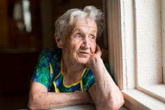 Grandma looks out the window. stock photos