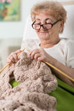 Grandma lying in bed and knitting Royalty Free Stock Image