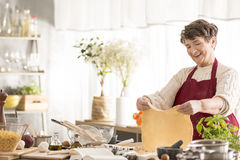 Grandma making a dough. Happy grandma making a pizza dough in her kitchen stock photos