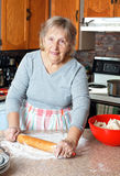 Grandma making pies. Senior woman or grandma rolling dough to make pies in her kitchen stock photography