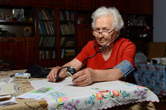 Grandma measures the pressure. Grandmother have glasses, she sits at the table at home Stock Photo