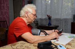Grandma measures the pressure. Grandmother have glasses, she sits at the table at home Stock Image