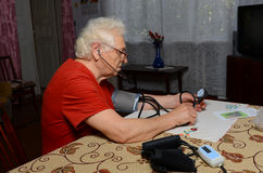 Grandma measures the pressure. Grandmother have glasses, she sits at the table at home Stock Photos
