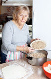 Grandma meat pie. Senior woman or grandma preparing meat pie ifor the holidays in her kitchen stock photo