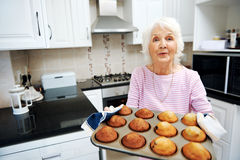 Grandma offerinf muffins Stock Images