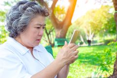 Grandma or older woman practice playing social media by using smartphone. Grandmother gets confused about high technology. Old royalty free stock photos