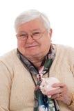 Grandma with piggy bank Stock Image