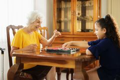 Grandma Playing Checkers Board Game With Granddaughter At Home. Happy little girl playing checkers with senior women at home. Family relationship with stock images