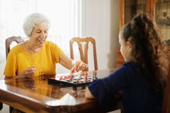 Grandma Playing Checkers Board Game With Granddaughter At Home. Happy little girl playing checkers with senior women at home. Family relationship with royalty free stock photo