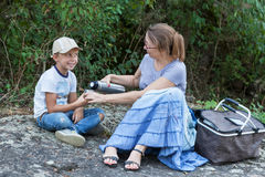 Grandma pours tea to grandson Stock Images