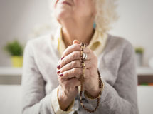 Grandma praying with rosary Royalty Free Stock Images