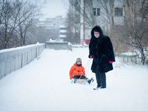 Grandma pulls sled with baby. Winter walk near the house. royalty free stock photo
