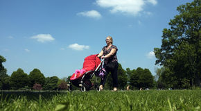 Grandma pushing a pushchair. A grandmother pushes her grandchild's pushchair in one of the many local parks of London Stock Photography