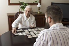 Grandma puts tarot grandson.  Age fairy puts tarot cards. Very old women puts a men tarot cards Stock Photos