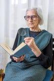 Grandma reading a book through magnifying glass Royalty Free Stock Photo