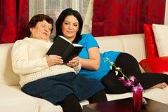 Grandma reading book to granddaughter. Grandma reading from a book to her adult granddaughter in living room Stock Image