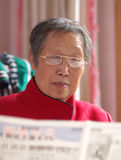 Grandma reading newspaper. Asian grandma reading newspaper at home Stock Image