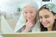 Grandma reading to grand daughter at home Royalty Free Stock Images