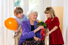 Grandma receives flowers from grand kids Stock Photography