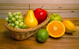 Grandma`s Basket of Assorted Fresh Fruits. Grapes, pear, apples, lime, orange, and lemon fruits in a wicker basket Royalty Free Stock Photography