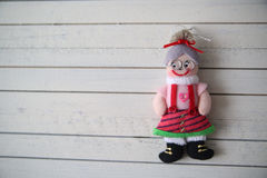 Grandma's doll rests on a wooden background. Christmas toy on a wooden background Stock Image