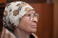 Grandma in scarf and glasses. Lonely grandma in scarf and glasses looking aside royalty free stock photos