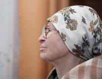Grandma in scarf and glasses. Lonely grandma in scarf and glasses looking aside royalty free stock image