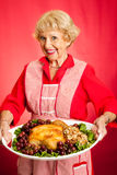 Grandma Serves Holiday Dinner Royalty Free Stock Images