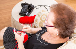 Grandma sitting knitting near the phone Stock Photo