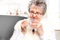 Grandma smelling perfume Royalty Free Stock Images