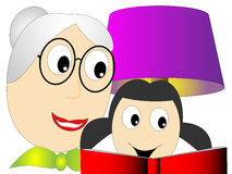 Grandma or teacher reads a little girl book Royalty Free Stock Photo