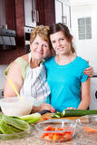 Grandma teen granddaughter. Happy grandma and teen granddaughter portrait in kitchen royalty free stock photography