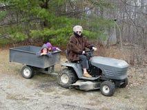 Grandma trucking grandkids. Grandmother transporting her grandchildren by tractor stock photography