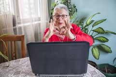 Grandma using laptop, camera and earphones for distant connections stock photo