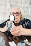 Grandma using magnifying glass to determine pill name Royalty Free Stock Photography