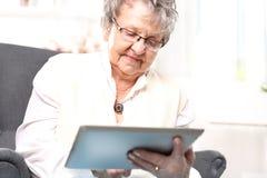 Grandma woman with a tablet. Elderly woman surfs the internet Stock Photos