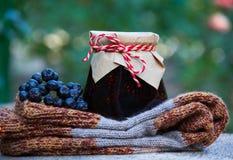 Grandma's gift. Homemade jam, knitted woolen socks and black chokeberry. Royalty Free Stock Photos