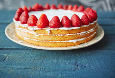 Grandmas Desert on Rustic Table. Closeup of delicious simple biscuit cake decorated with fresh ripe strawberries on top and white icing between layers standing Royalty Free Stock Photo