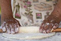 Grandmas hands. Very aged woman's hands rolling the dough Stock Photography