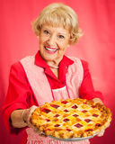 Grandmas Homemade Cherry Pie. Sweet grandmother in vintage apron holding a delicious homemade cherry pie Stock Photo