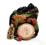 Grandmas Purse. An early 1900's antique beaded handbag along with an antique tapestry compact, antique lipstick, and an antique perfume bottle that was made in Royalty Free Stock Photo