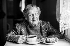 grandmaster Starsza kobieta pije herbaty siedzi przy stołem z ciastami zdjęcie stock