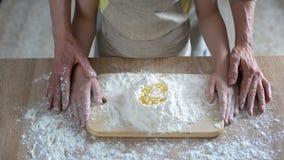Grandmom carefully teaching granddaughter kneading dough, family recipe, cooking. Stock photo stock photos