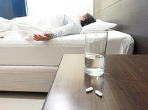 Grandmom sleeping in weakness concept, focus on medicine and gla Royalty Free Stock Photo