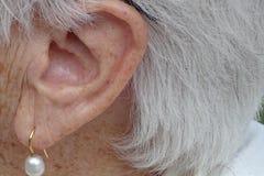 Grandmother& x27; 有详细耳环的s耳朵 库存图片