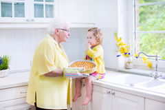 Grandmother and adorable girl baking pie in white kitchen. Happy beautiful great grandmother and her adorable granddaughter, curly toddler girl in colorful dress Stock Images