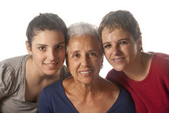 Grandmother with adult daughter and granddaughter. Embracing and looking at camera Royalty Free Stock Images