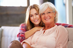 Grandmother With Adult Granddaughter Relaxing On Sofa Royalty Free Stock Image