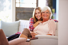 Grandmother With Adult Granddaughter Relaxing On Sofa Stock Photos