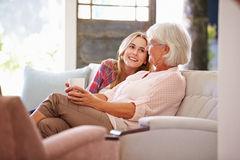 Grandmother With Adult Granddaughter Relaxing On Sofa Royalty Free Stock Photo